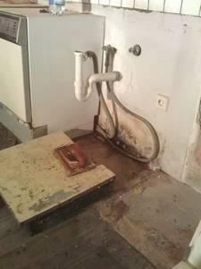 Schimmel an der Wand hinter/unter dem Spülenschrank um den Boiler herum. Der Boiler stand auf dem Stück Holz auf dem Boden des Spülenschranks, der wohl schon vor langer Zeit etwas eingebrochen war und somit an Höhe verloren hatte.