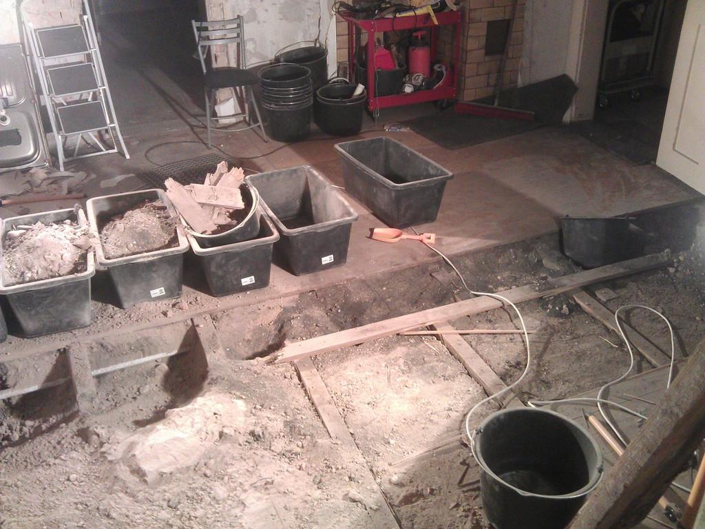 Grabungsstätte in der Küche vom Durchgang zum Forum (Weinstube) her gesehen, im Vordergrund die Betonplatte, dahinter die Wasserleitung vor den Mörtelwannen und im Hintergrund rechts der Kamin (Orientierung)