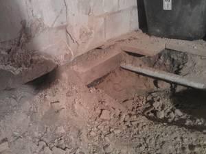 Füllmaterial/Schutt/Dreck unter Dielenboden an Wasserleitung mit Kalkziegelwand.