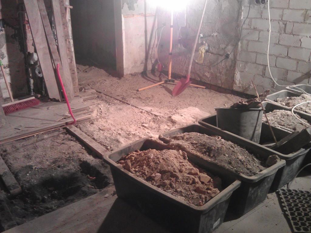 Abriss des Dielenbodens in der Küche, Zwischenstand am 23. September 2014 ca 21 Uhr. Im Vordergrund/rechts  die Mörtelwannen (60l) mit dem Aushub unter dem Dielenboden. Bild mitte links der alte Dielenboden auf Balken, mitte/hinten der freigelegte Betonboden im Anbauteil der Küche,