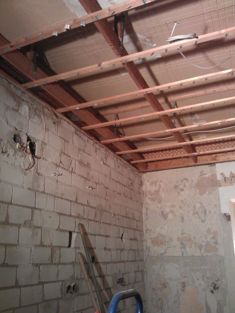 Loch der kleinen Dunstabzugshaube (schwarzer Fleck im Bild links, halbe Höhe), gesehen von den Fenstern aus entlang der Außenwand (Bild rechts unten bis Bildmitte) Richtung Wohnzimmerwand (Bild unten rechts). Oben die Lattung der um ca 40cm abgehängten Decke.