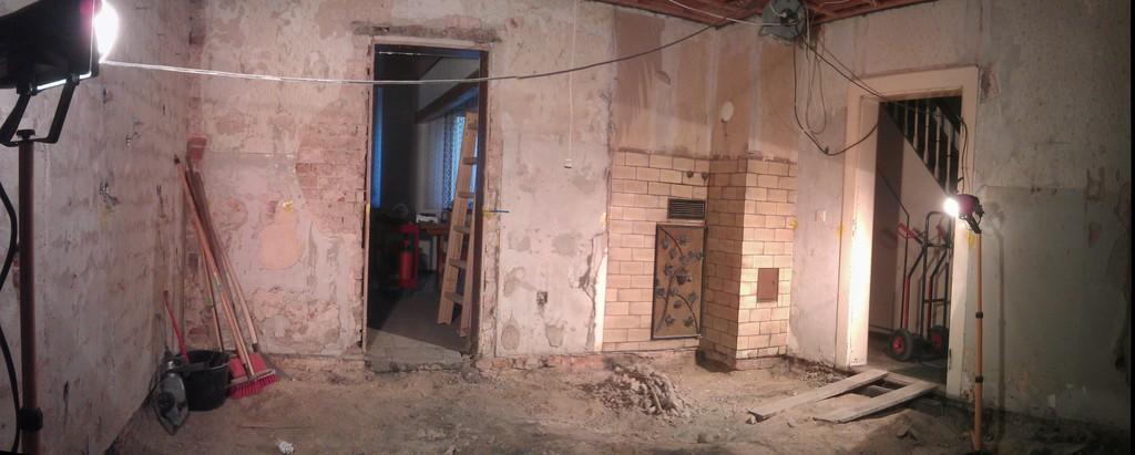Weitwinkel-Aufnahme (Panorama) der Küchenwand um den Kamin herum, fotografiert von der Tür zum Durchgang aus. Es fehlt nun der historische Fliesenboden und die Betonplatte vor dem Kamin.